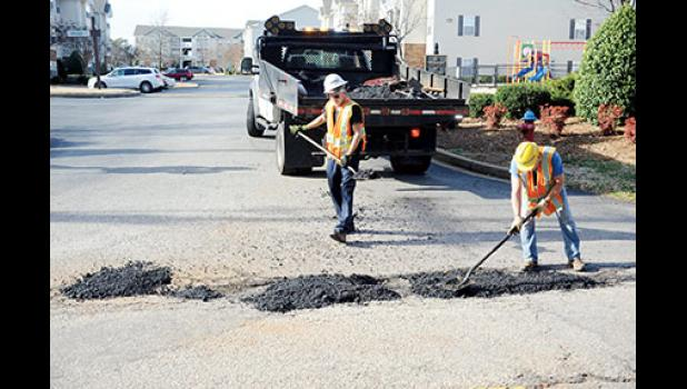 SCDOT workers patch potholes on Jones Avenue in Greer Monday afternoon.