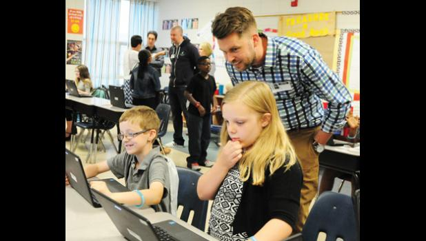 Chris Blair, center, assists Carter Presley, left, and Hannah Watson with a math assignment on the computer.