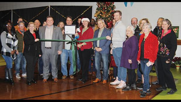 Caroline Robertson, Executive Director of Greer Relief, cut the ribbon Monday to celebrate the opening of this year's Christmas Morning Shoppe at the Greer First Baptist gymnasium.