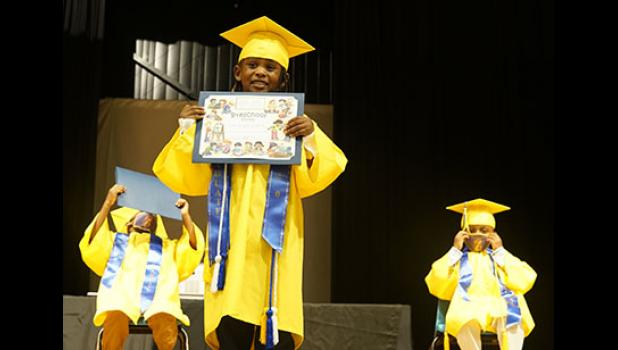 Six preschool graduates recently received certificates recognizing their accomplishments at Small Impressions.