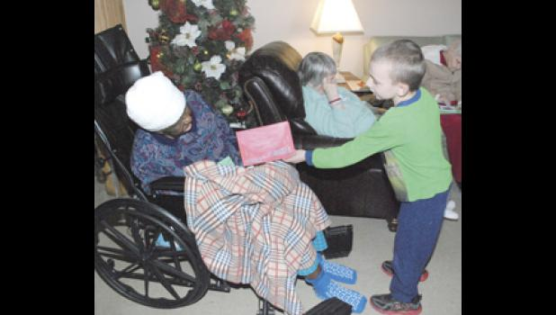 A Wellford Academy student delivers a handmade Christmas card to a Midway resident.