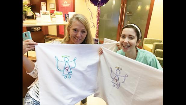 Pam Wrobel, left, and Bella Muntean with the first set of pillowcases to be filled with gifts and donated in April 2017.