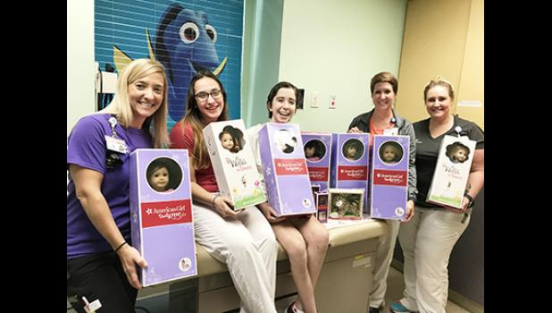 Bella Muntean (center) delivering American Girl dolls to the staff of Cleveland Children's Cancer Center, where she is receiving treatments.