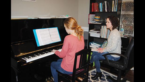 Piano teacher Sarah Plyler gives a piano lesson in Greer.