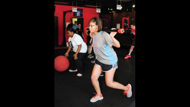 Cierra Hill performs lunges during her circuit at 9 Round Friday.