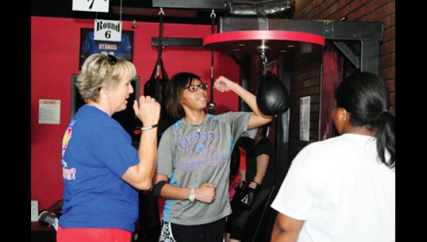Debbie Holcombe gives Hill pointers during a workout session at  9 Round in Greer.