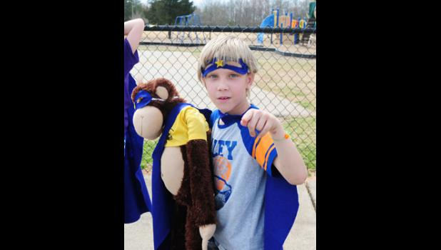 Classmate Gabriel Fisher  poses in a super hero costume with Cocoa.