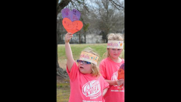 Students wave heart-shaped signs during the procession.