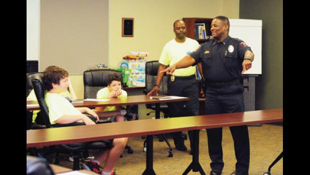 """Lt. Marcus Kelley critiques a crime scene reenactment, stressing the importance of providing detailed information when calling to report a crime. According to Lt. Jimmy Holcombe, the Youth Leadership Camp will help """"build the bridge"""" between youth and the police department."""