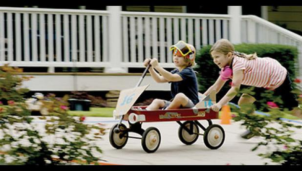 """Faith Renee Kennedy, who stars as Gracie Weathers in the movie """"Champion,"""" pushes Maddox Robinson on a wagon."""