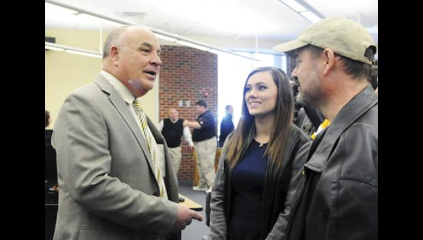 Eastside football coach Steve Wilson, left, meets Katlyn, center, and David Hinson during the schools introduction celebration Monday morning.