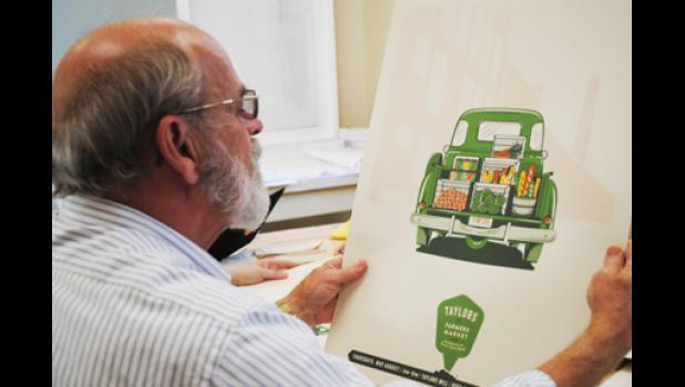 Steve Rhodes takes a look at the Taylors Farmers Market logo at a recent meeting.