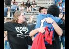 Davis' family receives a hug from a Byrnes football player during a memorial service at Nixon Field on Friday.
