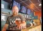 Matt Bowes stands at the helm of his new pub, Southern Growl, which offers 60 craft beers on tap.