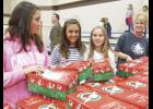 Emma Chacknes, Britton Smith, Emma Huskamp, and Julie Roberts (left to right) choose Operation Christmas Child shoeboxes to send to needy kids around the world.