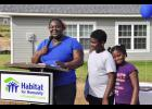New homeowner Stacey Greene, left, (with her children, D'Andre and Nateyah Kirksey) speaks to the crowd at the ceremonial wall raising of her new home Thursday.