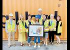 Greer High's Sara Cagle, center, visited the Inland Port after the Ports Authority purchased her mixed media painting of the facility.