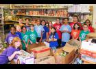 Top earning students from each of the fourth grade classes  of Lyman Elementary stand with donated canned goods at the Greer Soup Kitchen.