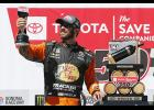 Martin Truex Jr., driver of the #19 Bass Pro Shops Toyota, poses with the trophy in Victory Lane after winning the Monster Energy NASCAR Cup Series Toyota/Save Mart 350 at Sonoma Raceway on June 23, 2019 in Sonoma, California.