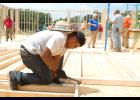 Volunteers bustle behind Sean Bing as he hammers a nail into the wall framing at the Three Rivers Baptist Association Mission Center last week.