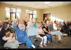 Community members raise their hands to indicate their desire to speak during last week's public hearing on the proposed road closure for a portion of Victor Avenue Extension.
