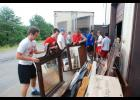 A group of Riverside High School football players help organize showroom products at Bargain Furniture and More off South Buncombe Road in Greer.