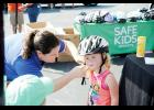 Lee Penny, manager of Safe Kids Upstate, (left) helps fit Cooper Kellett into a bike helmet during the Sgt. Brian Donnelly Memorial Safety Awareness Day last Saturday in Taylors.