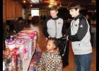 Jakerri Bowens looks over the selection of dolls with the help of volunteers  Sam Gravely and Andy Bryson.