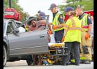 Injury assistance: Greer police and fire workers help an injured woman onto a stretcher on Poinsett Street Monday afternoon.  The woman was one of several motorists injured in the three-car accident, which occurred at about 2 p.m.
